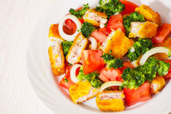 Fresh vegetable salad with fried breaded fish fillets Stock Image