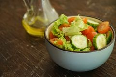 Fresh vegetable salad of green cucumbers, cherry tomatoes and iceberg lettuce, with olive oil in a deep plate. Fresh vegetable salad green cucumbers cherry royalty free stock images