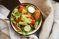 fresh vegetable salad of green cucumbers, cherry tomatoes and iceberg lettuce, with olive oil in a deep plate stock photo