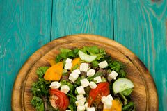 Fresh vegetable salad with greenery, cheese, tomatoes, cucumber. On a blue wooden table Royalty Free Stock Images