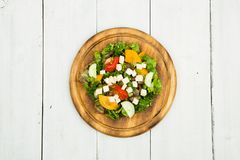 Fresh vegetable salad with greenery, cheese, tomatoes, cucumber. On a white wooden table Royalty Free Stock Photo