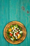 Fresh vegetable salad with greenery, cheese, tomatoes, cucumber. On a blue wooden table Stock Images