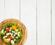 Fresh vegetable salad with greenery, cheese, tomatoes, cucumber. On a white wooden table Royalty Free Stock Images