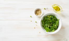 Fresh vegetable salad  with greens, cucumber , peas and pine nuts. On a white wooden background. Flat lay. Copy space royalty free stock photography