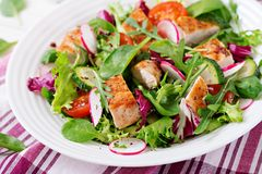 Fresh vegetable salad with grilled chicken breast   - tomatoes, cucumbers, radish and mix lettuce leaves. Chicken salad. Healthy food Royalty Free Stock Images
