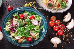 Fresh vegetable salad with grilled chicken breast - tomatoes, radish and mix lettuce leaves. Chicken salad. Healthy food. Black ba. Ckground. Top view Royalty Free Stock Image
