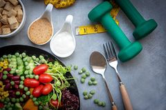 Fresh vegetable salad and healthy food for sport equipment for women diet slimming with measure tap for weight loss on black backg royalty free stock photography