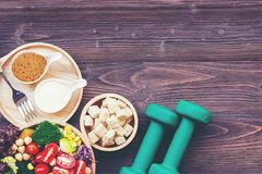 Fresh vegetable salad and healthy food for sport equipment for women diet slimming with measure tap for weight loss on wood backgr stock photos