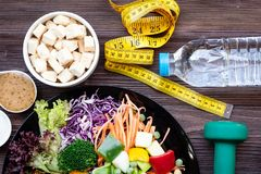 Fresh vegetable salad and healthy food for sport equipment for women diet slimming with measure tap for weight loss on wookd backg. Round. Healthy Sport Concept stock photos