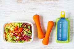 Free Fresh Vegetable Salad In Lunch Box With Orange Dumbbells Excercise Equipment And Energy Water Drink On White Rusty Wood Background Royalty Free Stock Photography - 150844697