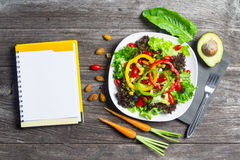 Fresh vegetable salad with notebook paper on wood royalty free stock images