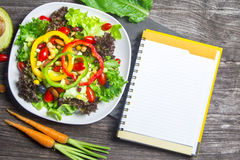 Fresh vegetable salad with notebook paper on wood Stock Photo