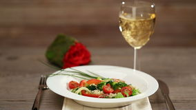 Fresh vegetable salad and pouring wine stock footage