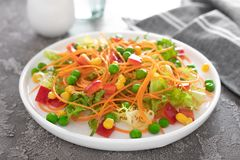 Fresh vegetable salad with raw carrot, green peas, corn, sweet pepper and lettuce. Healthy vegan, vegetarian lunch menu, closeup. Fresh vegetable salad with raw royalty free stock images