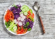 Fresh vegetable salad with red cabbage, cucumber, radish, carrots, sweet peppers, red onion and parsley on a white plate. Light on wooden rustic background Stock Photo