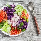 Fresh vegetable salad with red cabbage, cucumber, radish, carrots, sweet peppers, red onion and parsley on a white plate. On light wooden rustic background Royalty Free Stock Images