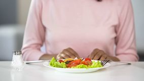 Fresh vegetable salad and saltshaker on dinner table, woman having lunch at home. Stock photo royalty free stock photo