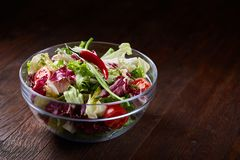 Fresh vegetable salad served in glass bowl over dark wooden background, selective focus, shallow depth of field. Fresh vegetable salad served in transparent stock photo