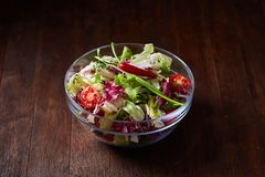 Fresh vegetable salad served in glass bowl over dark wooden background, selective focus, shallow depth of field. Fresh vegetable salad served in transparent stock photography