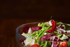 Fresh vegetable salad served in glass bowl over dark wooden background, selective focus, shallow depth of field. Fresh vegetable salad served in transparent Stock Photos
