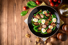 Fresh vegetable salad with spinach, cherry tomatoes, quail eggs, pomegranate seeds and walnuts in black plate on wooden table. Stock Photo