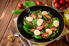 Fresh vegetable salad with spinach, cherry tomatoes, quail eggs, pomegranate seeds and walnuts in black plate on wooden table. Royalty Free Stock Photography
