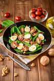 Fresh vegetable salad with spinach, cherry tomatoes, quail eggs, pomegranate seeds and walnuts in black plate on wooden table. Stock Images