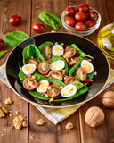 Fresh vegetable salad with spinach, cherry tomatoes, quail eggs, pomegranate seeds and walnuts in black plate on wooden table. Royalty Free Stock Photos
