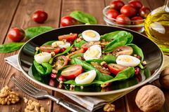 Fresh vegetable salad with spinach, cherry tomatoes, quail eggs, pomegranate seeds and walnuts in black plate on wooden table. Stock Image