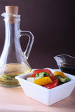 Fresh vegetable salad with tomato, cucumber, bell pepper, lettuce leaf in white bowl, olive oil and balsamic souce in. Bottle. Selective focus stock images
