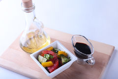 Fresh vegetable salad with tomato, cucumber, bell pepper, lettuce leaf in white bowl, olive oil and balsamic souce in. Bottle. Selective focus royalty free stock image