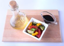 Fresh vegetable salad with tomato, cucumber, bell pepper, lettuce leaf in white bowl, olive oil and balsamic souce in. Bottle. Selective focus royalty free stock photography