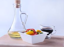 Fresh vegetable salad with tomato, cucumber, bell pepper, lettuce leaf in white bowl, olive oil and balsamic souce in. Bottle. Selective focus stock photo