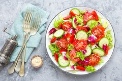 Fresh vegetable salad with tomatoes, cucumbers, sweet pepper and sesame seeds. Vegetable salad on white plate. Stock photo Stock Image