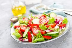Fresh vegetable salad with tomatoes, cucumbers, sweet pepper and sesame seeds. Vegetable salad on white plate. Stock photo Stock Images