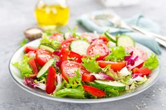 Fresh vegetable salad with tomatoes, cucumbers, sweet pepper and sesame seeds. Vegetable salad on white plate. Stock photo Stock Photography