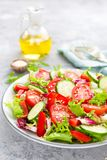 Fresh vegetable salad with tomatoes, cucumbers, sweet pepper and sesame seeds. Vegetable salad on white plate. Stock photo Royalty Free Stock Photography