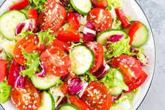 Fresh vegetable salad with tomatoes, cucumbers, sweet pepper and sesame seeds. Vegetable salad on white plate. Stock photo Royalty Free Stock Image