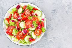 Fresh vegetable salad with tomatoes, cucumbers, sweet pepper and sesame seeds. Vegetable salad on white plate. Stock photo Royalty Free Stock Photo