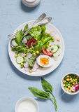Fresh vegetable salad with tomatoes, radish, green herbs and boiled egg on a light blue stone background. Healthy Breakfast or sna. Ck. Healthy food Royalty Free Stock Photos