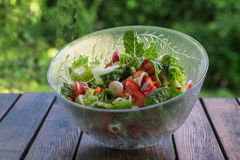 Fresh vegetable salad in transparent bowl. Bokkeh Royalty Free Stock Photos