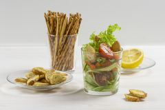 Fresh vegetable salad in a transparent glass on white. Cherry tomatoes cucumbers lettuce croutons, lemon juice dressing. Salty stock image