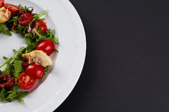 Fresh vegetable salad in a white plate on black background. Healthy salad with Sun dried tomatoes, Arugula and Balsamic. Stock Photo