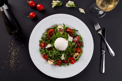Fresh vegetable salad in white plate on black. Healthy salad with Sun dried tomatoes, Arugula, Mozzarella and Balsamic. Royalty Free Stock Image