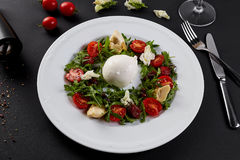 Fresh vegetable salad in white plate on black. Healthy salad with Sun dried tomatoes, Arugula, Mozzarella and Balsamic. Fresh vegetable salad in a white plate Stock Photography
