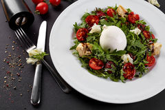 Fresh vegetable salad in white plate on black. Healthy salad with Sun dried tomatoes, Arugula, Mozzarella and Balsamic. Fresh vegetable salad in a white plate Royalty Free Stock Photo