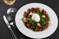 Fresh vegetable salad in white plate on black. Healthy salad with Sun dried tomatoes, Arugula, Mozzarella and Balsamic. Royalty Free Stock Photos