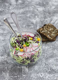 Fresh vegetable salad with white and red cabbage, cucumber, radish and cilantro in a glass jar on a stone texture. Royalty Free Stock Photo