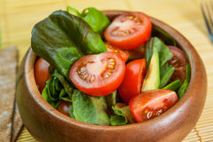 Fresh vegetable salad in wooden bowl on bamboo napkin with crisp. Fresh vegetable salad of salad leaves and tomatoes Stock Photo