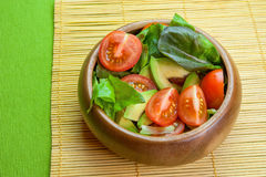 Fresh vegetable salad in wooden bowl on bamboo napkin with crisp. Fresh vegetable salad of salad leaves and tomatoes Royalty Free Stock Photo